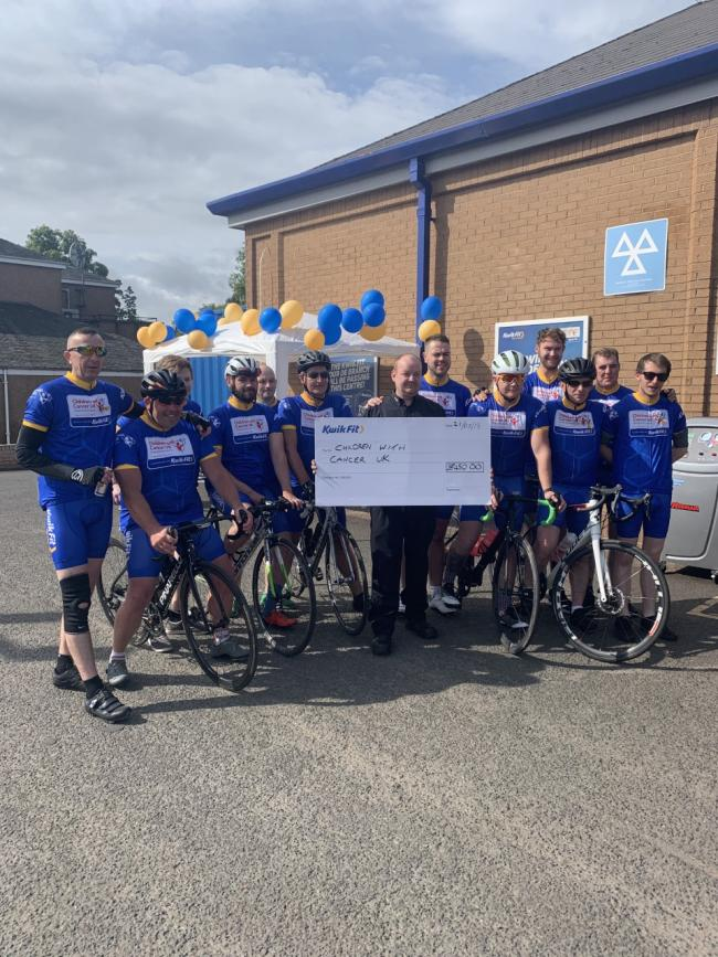 Kwik Fit's Giffnock branch manager Martin Meechan presents a cheque to the team of cyclists
