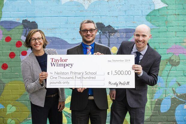 Kirsty McGill, of Taylor Wimpey West Scotland, hands a cheque to Gerard Curley and Andrew Howie