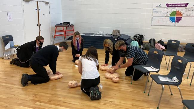 Daryl Campbell (right) teaches Barrhead High pupils how to perform cardiopulmonary resuscitation (CPR)
