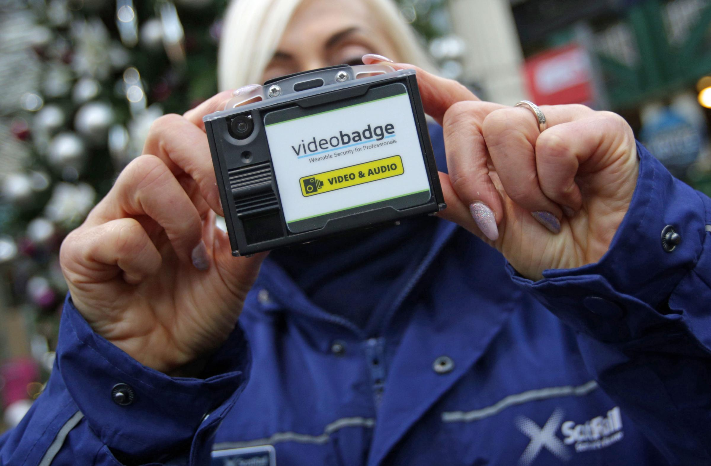 A member of ScotRail staff holds a new body-worn CCTV camera at Waverley Station